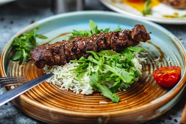 Espetos de carne de lado vista grelhados de carne com arroz e rúcula em um prato