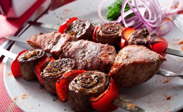 Espetos de carne de porco e legumes grelhados, conceito de comida saudável, foco seletivo no fundo de madeira.