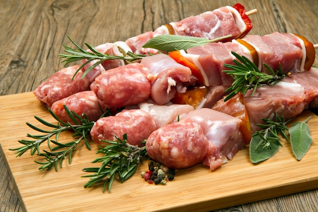 Espetos de carne e pimenta em uma tábua de madeira