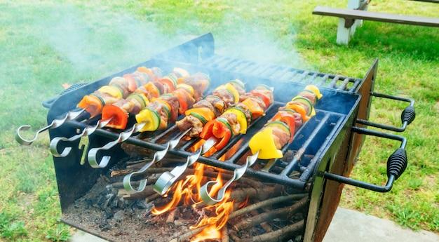 Espetos de carne e vegetais na grelha na natureza