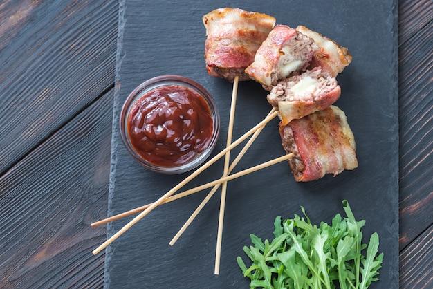 Espetos de carne embrulhados em bacon recheados com mussarela