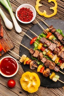 Espetos de carne grelhada com legumes na mesa de madeira