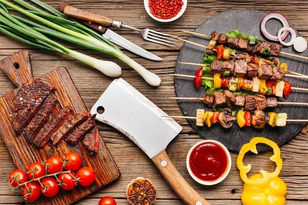 Espetos de carne grelhada e bife com legumes na mesa de madeira