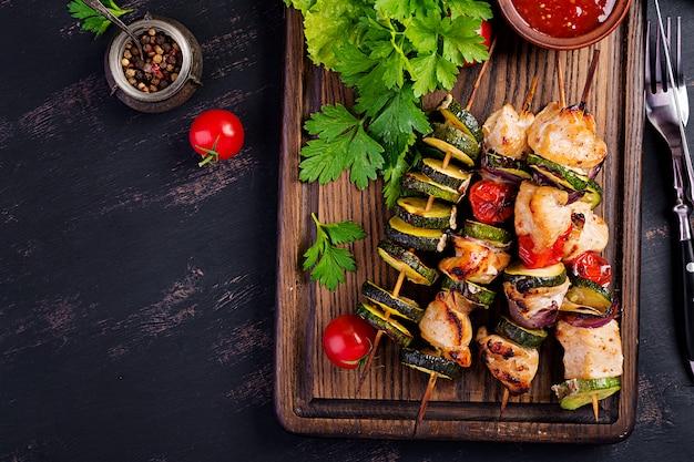 Espetos de carne grelhada, espetinho de frango com abobrinha, tomate e cebola vermelha