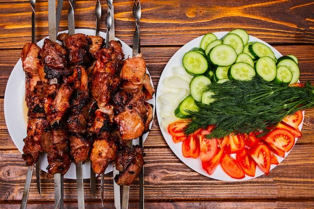 Espetos de carne grelhada no churrasco fritos no fogo, amarrados em varas de metal em um prato sobre a mesa para refeições prontas.
