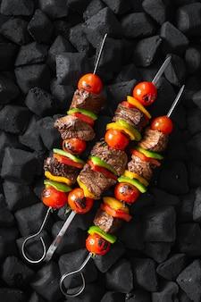 Espetos de carne sendo grelhados em uma vista superior de brasas