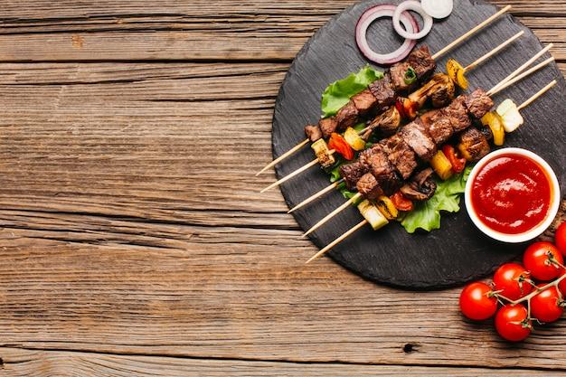 Espetos de churrasco com carne e vegetais na ardósia preta circular