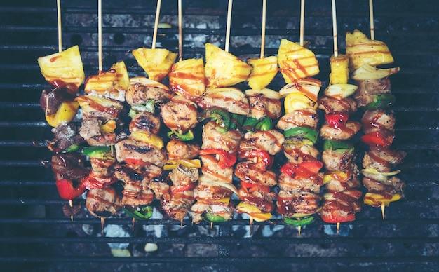 Espetos de churrasco de carne e vegetais grelhados sobre o fundo preto, vista superior