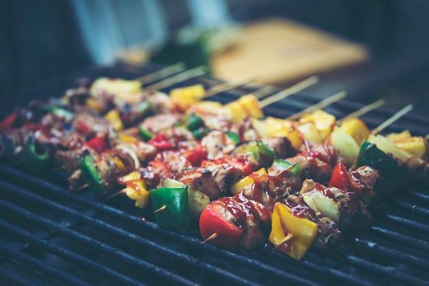 Espetos de churrasco de carne e vegetais grelhados sobre o fundo preto