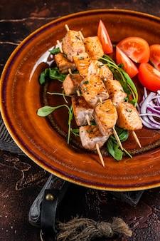 Espetos de churrasco de salmão no prato rústico com legumes. fundo escuro. vista do topo.