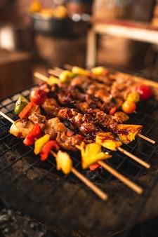 Espetos de churrasco grelhados em churrasqueiras a carvão em casa