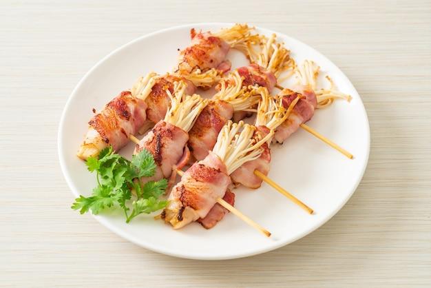 Espetos de cogumelo com agulha dourada embrulhada com bacon