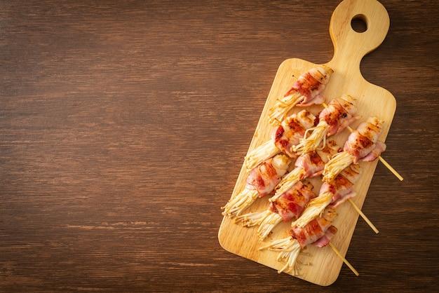 Espetos de cogumelo com agulha dourada envolvida com bacon