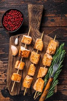 Espetos de espetinho de salmão grelhado na placa de madeira. fundo de madeira escuro. vista do topo.