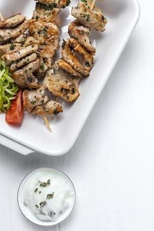 Espetos de frango caseiro com ervas aromáticas e especiarias com molho de iogurte. comida árabe