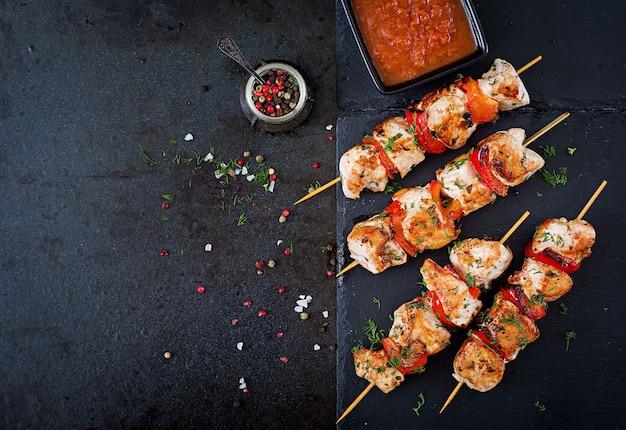 Espetos de frango com fatias de pimentão e endro. comida saborosa. refeição de fim de semana. vista do topo. postura plana.