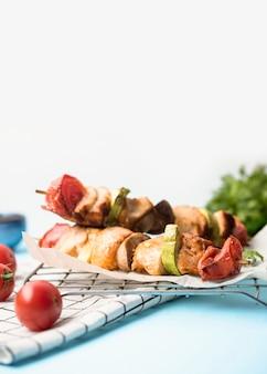 Espetos de frango de frente em papel pergaminho com tomate cereja