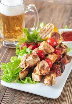 Espetos de frango grelhado com caneca de cerveja