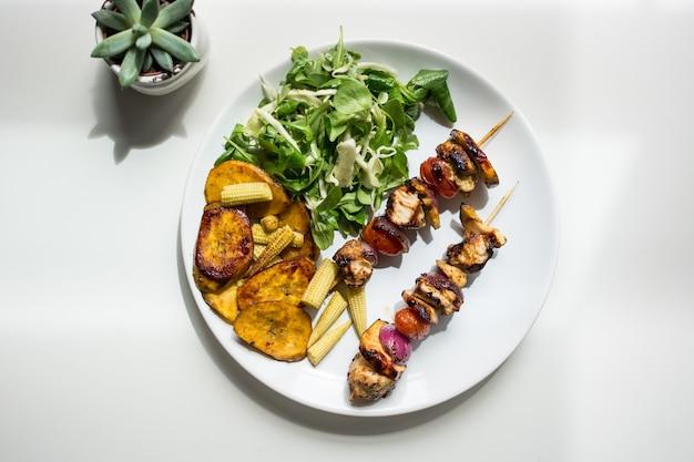 Espetos de frango grelhado com salada de cordeiro e milho de bebê