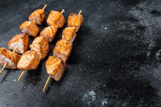 Espetos de kebab de salmão grelhado. fundo preto. vista do topo. copie o espaço.