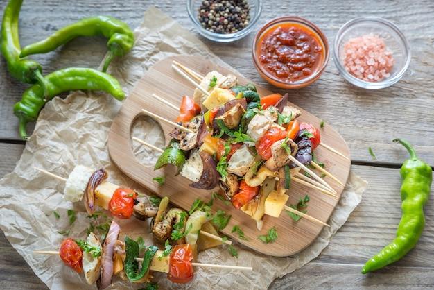 Espetos de legumes grelhados na placa de madeira