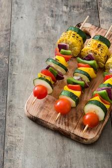 Espetos de legumes na mesa de madeira