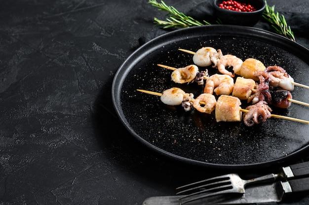 Espetos de madeira com camarão, polvo, lula e mexilhões. kebab com frutos do mar ..