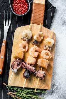 Espetos de madeira com frutos do mar grelhados, camarão, polvo, lula e mexilhões.