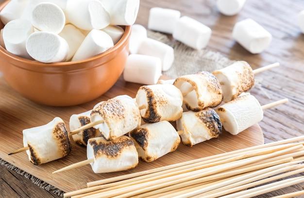 Espetos de marshmallow na placa de madeira
