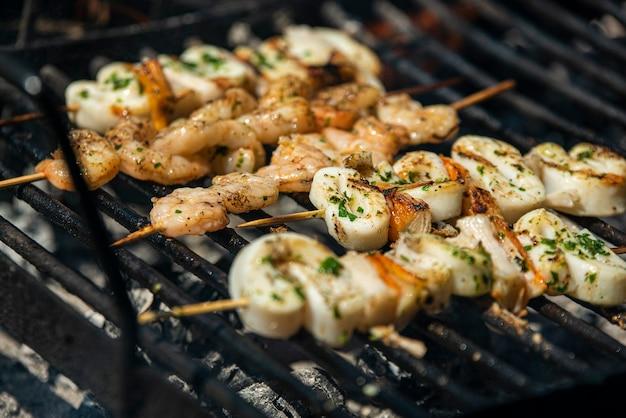 Espetos de peixe com camarão e lula na grelha