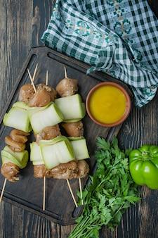 Espetos em um espeto com abobrinha com molho, legumes e ervas sobre uma tábua.