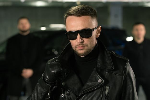 Espião ou gângster de óculos escuros, luvas de couro pretas e jaqueta e sua gangue ou guarda-costas no fundo