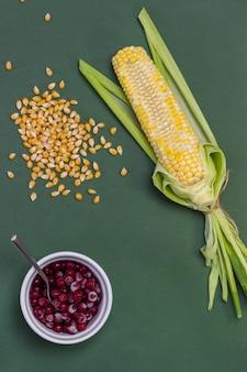 Espiga de milho com grãos cortados. grãos de milho na mesa. bagas vermelhas em tigela branca. fundo verde. postura plana