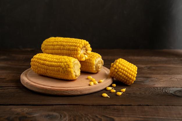 Espiga de milho com mentiras no fundo da mesa de madeira da placa da placa de corte redondo. copie o espaço para o texto.