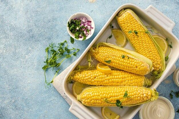 Espiga de milho crua na assadeira para preparar comida vegetariana saudável, vista superior