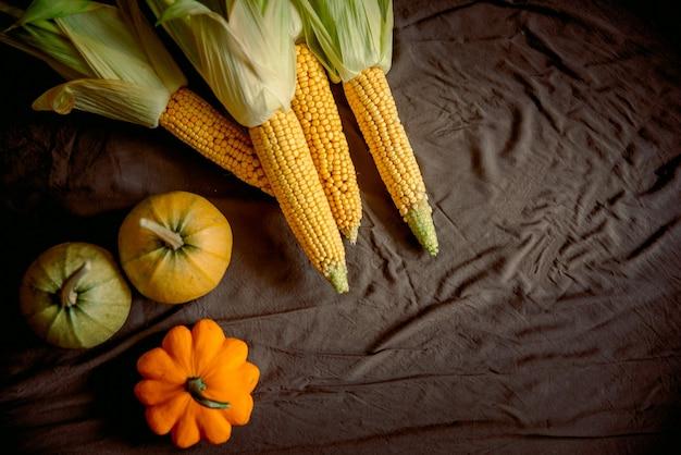 Espiga de milho em fundo de linho marrom, vista superior do outono, close-up, plano leigo, copie o espaço.