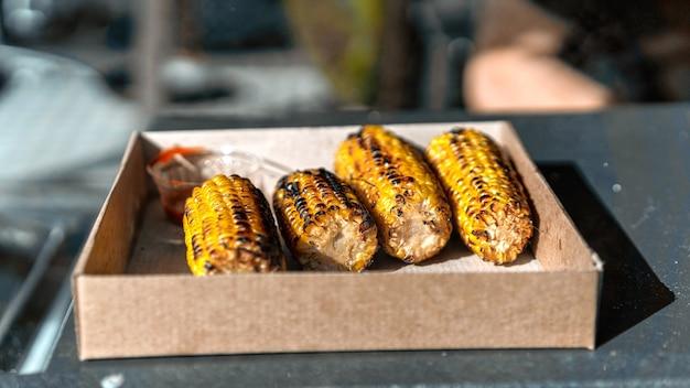 Espiga de milho frita em um pedido. bbq. comida de rua