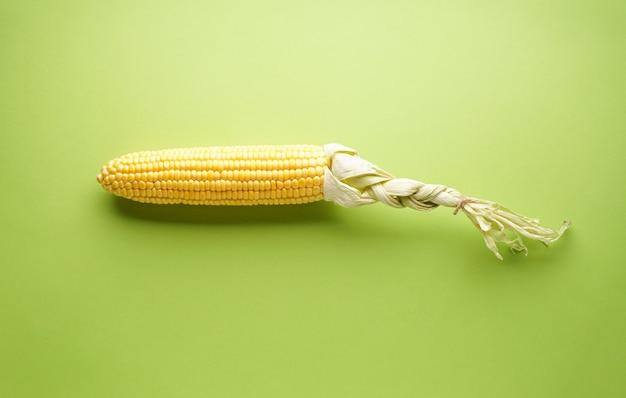 Espiga de milho maduro sobre um fundo verde, vista superior.