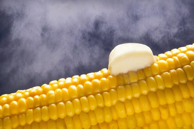 Espiga de milho quente com pedaço de manteiga. vapor.