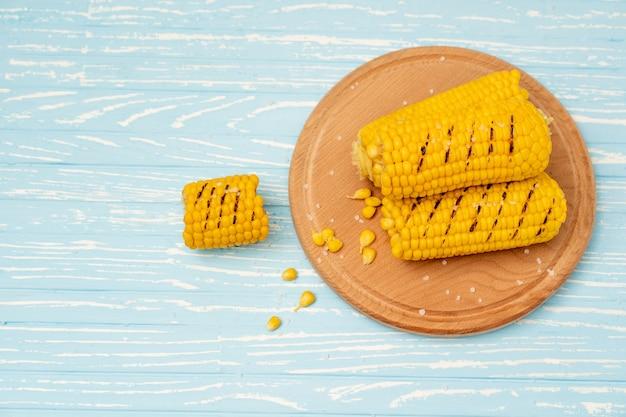 Espiga de milho quente grelhada encontra-se no fundo da mesa de madeira azul da placa da placa de corte redondo. copie o espaço para o texto.