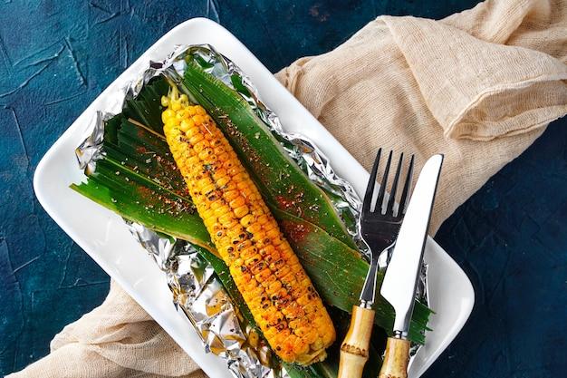 Espigas de milho cozidas em fogo aberto milho doce torrado com especiarias vista de cima plana vegetais grelhados ...