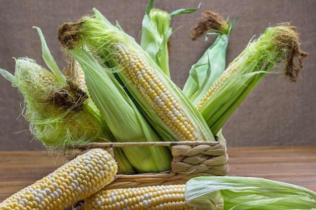 Espigas de milho cru com seda de milho e folhas na cesta de vime. fundo de madeira.