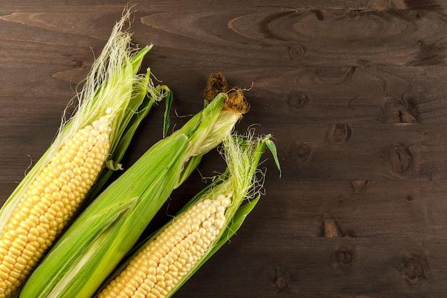 Espigas de milho cru em uma mesa de madeira escura. vista do topo.