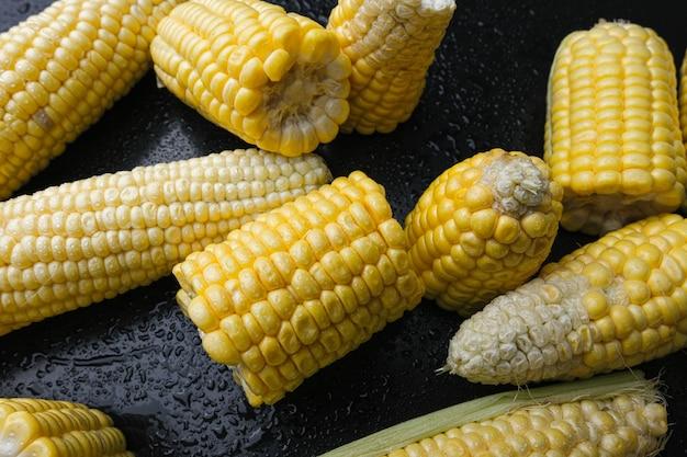 Espigas de milho doce cru frescas em fundo preto. fechar-se.