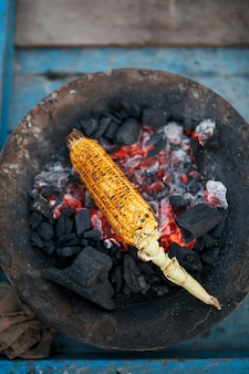 Espigas de milho douradas sobre os carvões na grelha. na praia de arambol ao pôr do sol. asiática, comida de rua indiana