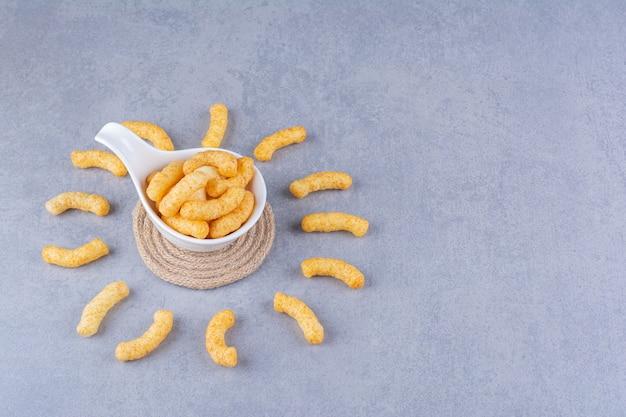 Espigas de milho em uma colher no tripé no azul.