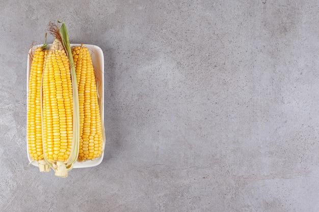 Espigas de milho frescas e doces isoladas em um prato branco