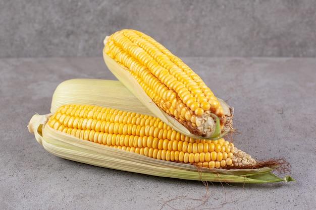Espigas de milho frescas em uma superfície cinza