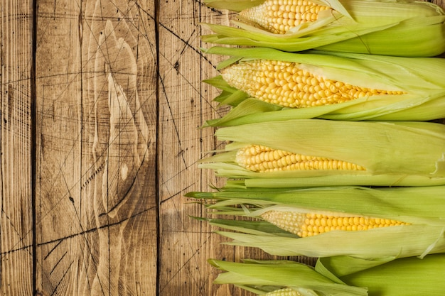 Espigas de milho frescas na tabela de madeira rústica, close up.