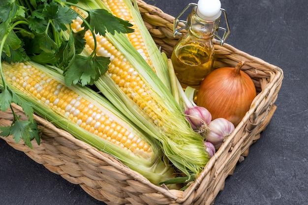 Espigas de milho frescas, salsa verde, óleo na garrafa e alho na cesta de vime. fechar-se. fundo preto. postura plana